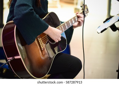 Close up of people playing guitar.
