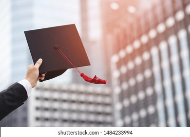 close up people show hand hold show hat in background School building. Shot of graduation cap during Commencement University Degree Concept , Celebration Education Student Success Learning Concept.