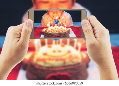 Close up of people take photo of a boy ready to blow birthday cake party using mobile phone - happy birthday celebration concept