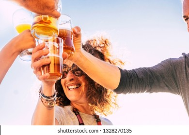 Close up of people toasting and clinking together with happy and joy and having fun - cheerful people with beer and drinks laughing in friendship - middle age vacation and celebrate activity