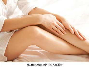 Close up of a perfect female legs. Woman applying moisturizer.