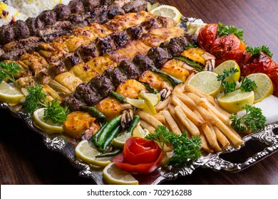 Close up of Persian Mix Kebab consisting of minced meat, chicken and steak with french fries (chips) on a large tray