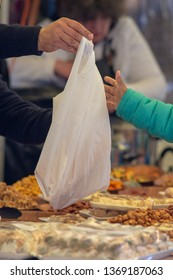 close up of person buying goods with white plastic bag