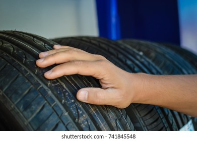 Close up of person checking examining car tyre on the shelf abstract transportation background. Automobile warehouse business, factory production. Protector surface texture