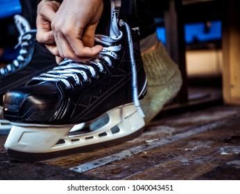close up person dressing ice hockey wear in locker room