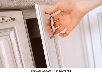 close up person  hand opens wooden shelf at home