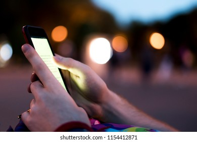 close up person hands holding phone and reading electronic book at night with bokeh
