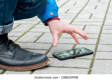 Close of a person picking up a lost mobile phone on street