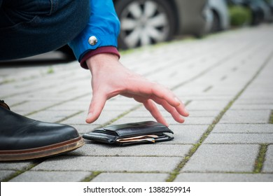 Close of a person picking up a lost wallet on street