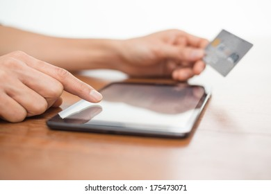 Close up of a person typing on a digital tablet device and holding a credit card while shopping online