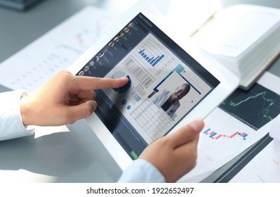 Close up of person video conferencing with colleagues on digital tablet, analyzing financial statistics displayed on the laptop screen.