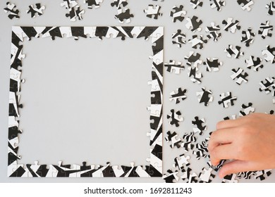 Close Up of Person Working on Black and White Puzzle From Above