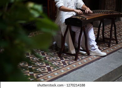 "Close up of a person's hand playing the Chinese musical instrument call the ""Guzheng"" or also known as the Chinese zither. It is a Chinese plucked string instrument"