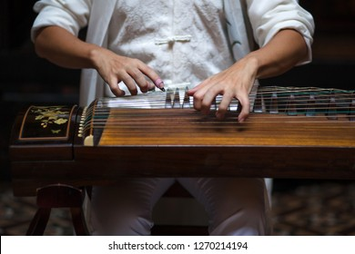 """Close up of a person's hand playing the Chinese musical instrument call the """"Guzheng"""" or also known as the Chinese zither. It is a Chinese plucked string instrument"""