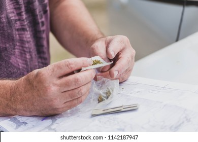 Close up of person's hands rolling a joint with marijuana (cannabis) and rice paper on top of a car hood. Travel map visible underneath.