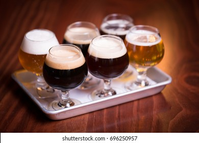 Close up perspective craft beer tasting flight at local brewery of small round tulip glasses in row on metal sheet tray with rainbow variety of golden yellow hoppy ales to dark malt stouts on bar