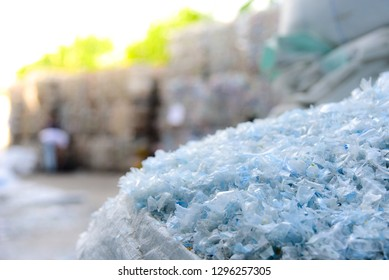 Close up PET plastic bottle flakes in white big bag with blur plastic bottle bales background