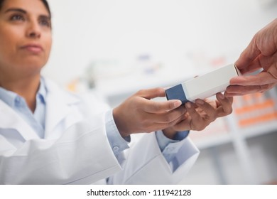 Close up of a pharmacist giving a box to someone in hospital ward
