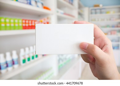 Close up pharmacist hand hold medicine box package with shelves of drugs in the pharmacy