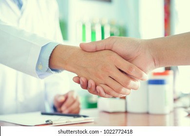 close up pharmacist man hand shaking at counter with patient customer after inform knowledge of correctly medicine usage in routine life and how to living for longer age at drug store , health concept