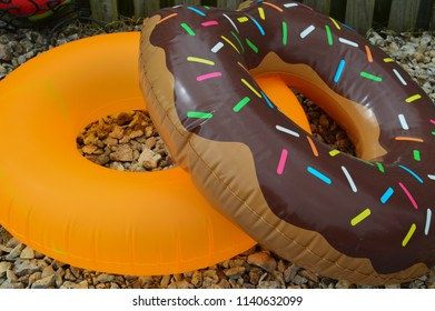Close up photo of 2 inner tube pool floaties. One is a doughnut, the other one is orange.