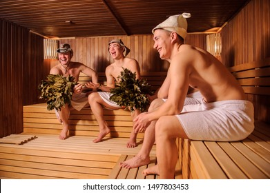 close up photo of 4 men resting in russian sauna using oak brooms