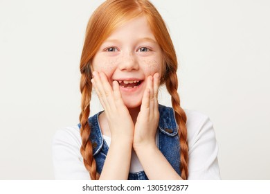 Close up photo of adorable smiling happy girl with braided red hair in two long plaits, keeps palms near her face, looking away,dressed in jeans overall isolated on white background