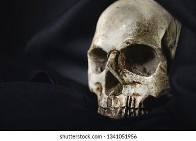 Close up photo af old skull covered in black robe