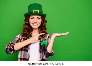 Close up photo of attractive she her brunette arm hand finger point to open palm promotional wearing casual checkered plaid shirt leprechaun headwear isolated green vivid bright vibrant background