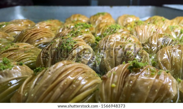close up photo of baklavas with pistachio nuts. Traditional desert in Turkey and is called baklava. Only the middle ones are in focus, rest not. Celebration food.