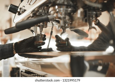 Close up photo of barista's hand pouring coffee into the measure glass at the coffee machine. Barista is holding a glass measuring coffee while preparing espresso at the coffee shop. Copyspace.