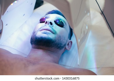Close up photo of a bearded man having protective glasses on his face and getting suntan in modern solarium