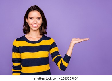 Close up photo beautiful amazing funky she her lady hold open palm hand arm indicating side empty space interesting novelty product wear blue yellow striped pullover isolated violet purple background