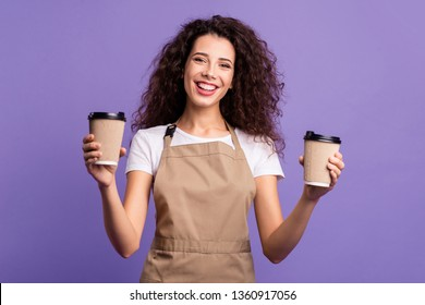 Close up photo beautiful amazing her she lady waitress owner cafeteria hold hands arms paper cups hot beverage invite visit cafe wear casual white t-shirt apron isolated violet purple background