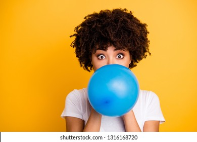Close up photo beautiful amazing she her dark skin lady hold air balloon eyes surprised stupor hiding face big eyes wear casual white t-shirt isolated yellow bright vibrant vivid background