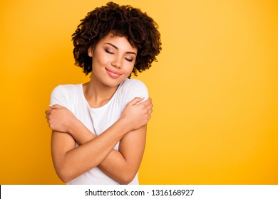 Close up photo beautiful amazing she her dark skin lady sweet remember best date ever imagination hug herself eyes closed wear casual white t-shirt isolated yellow bright vibrant background