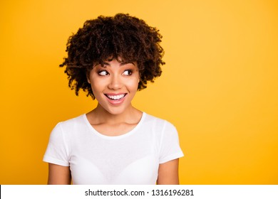 Close up photo beautiful amazing she her dark skin lady cool pretty look to empty space not sure but glad result wear casual white t-shirt isolated yellow bright vibrant vivid background