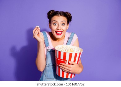 Close up photo beautiful amazing she her lady two buns watch tv show popcorn bucket mouth open thrill exciting plot wear casual t-shirt jeans denim overalls clothes isolated purple violet background