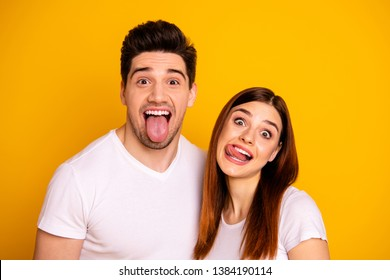 Close up photo beautiful amazing she her he him his guy lady pair tongue out mouth  careless funny funky foolish making stupid facial expressions wear casual white t-shirts isolated yellow background
