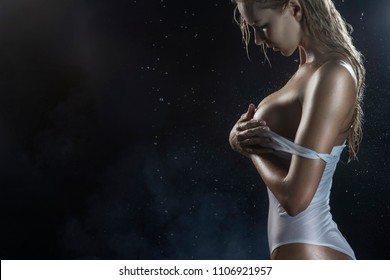 Close up photo of beautiful athletic blonde girl breast with wet oiled body wearing white translucent sexy swimsuit posing sideways in scenic smoke under falling water drops on black. Copy space