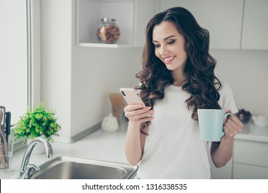 Close up photo beautiful brunette she her lady homey indoors watch telephone hold beverage glad check email wearing domestic home apparel clothes outfit comfy table kitchen
