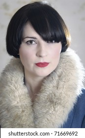 Close up of photo of a beautiful dark-haired young woman wearing a coat with a fake fur collar.