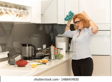 Close up photo beautiful frustrated woman in bad mood with a helpless expression on face and hands in the air in frustration looking at dirty plates kitchen as she hates dislike clean up the house.