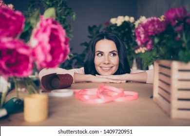 Close up photo beautiful funny funky she her lady face leaning hands arms table many vases pink ribbon composition handmade bunch fresh flowers condition opening small flower shop room indoors