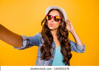 Close up photo beautiful her she wavy lady  hands arms sun hat make take selfies send air kiss instagram followers wear specs blue teal green everyday jacket clothes isolated yellow background