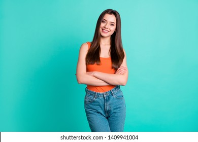 Close up photo beautiful her she lady hold arms hands folded ideal lips sincere self-confident easy-going great mood wear casual orange tank-top jeans denim isolated bright teal turquoise background