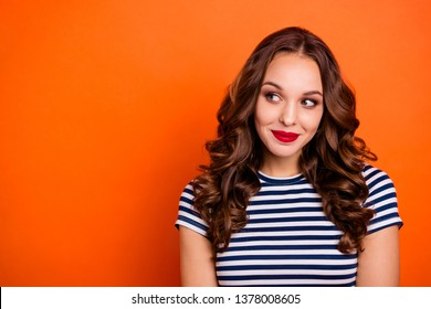 Close up photo beautiful she her lady allure tempting red lips intelligent sincere eyes look side empty space delighted wear casual striped white blue t-shirt clothes isolated orange bright background