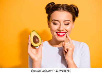 Close up photo beautiful she her lady pretty hairdo hold slice avocado look side with interest hand arm finger chin yummy tasty wear casual white pullover clothes isolated yellow background