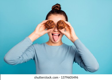 Close up photo beautiful she her lady hide eyes advising buy buyer try new yummy just baked tasty cacao color muffins tongue out mouth wear casual sweater pullover isolated blue bright background