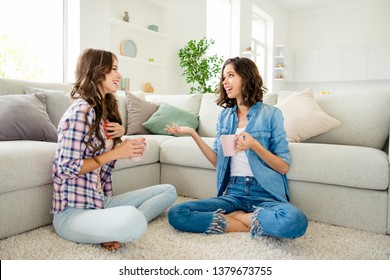 Close up photo beautiful she her ladies buddies fellows meeting hot beverage hands arms sharing news rumours wear casual jeans denim checkered plaid shirts apartments sit floor divan room indoors